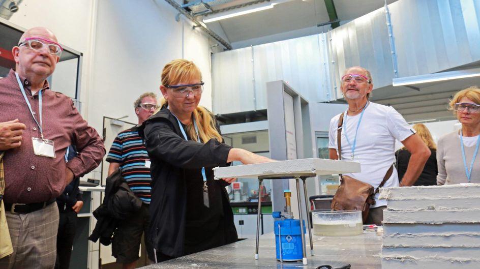 Gut isoliert: Besucherin Johanna Kröll testet die Wärmedämmung von CALOSTAT®. Obwohl der Bunsenbrenner dem Material ganz schön einheizt, kann sie die Hand auf den oberflächlich nur lauwarmen Baustoff legen.