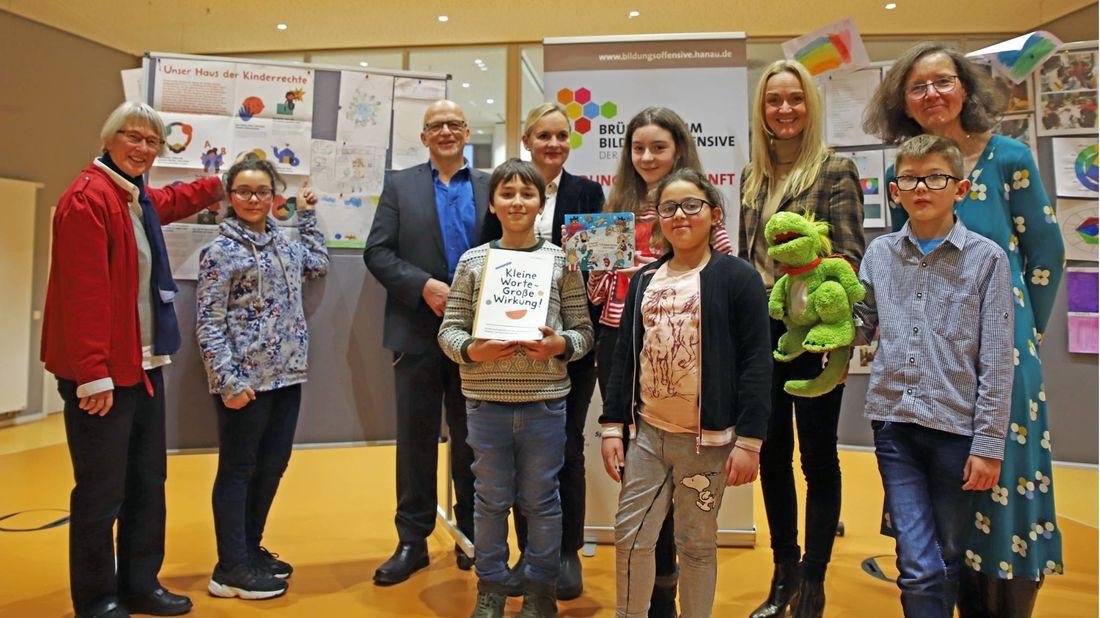 Stolz präsentieren die Kinder Bürgermeister Axel Weiss-Thiel, 3. v. l., Susanne Peitzmann von der Evonik Stiftung, 5. v. l., und Standortleiterin Kerstin Oberhaus, 8. v. l., ihre Schatzkammer des Wissens.