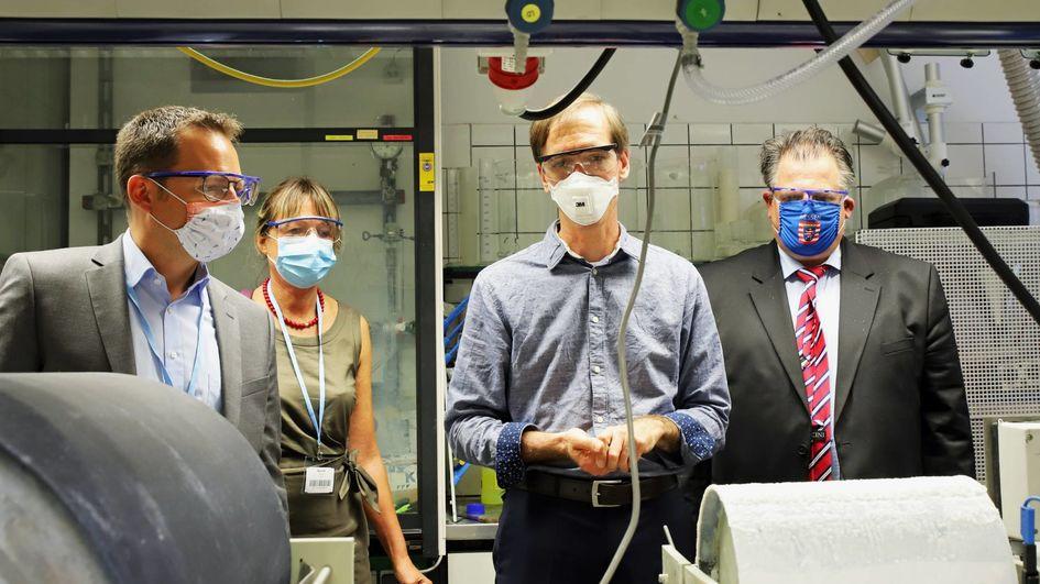 Besuch in der Verfahrenstechnik: Patrik Stenner zeigt den Abgeordneten wie er Mikropartikel aus Abwasser abscheidet.